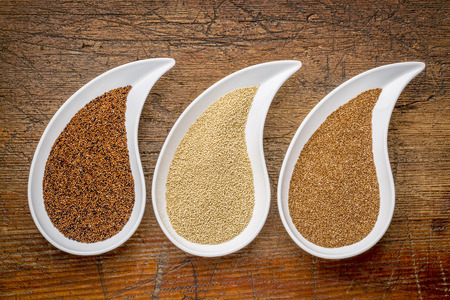 teardrop: three tiny gluten free grains - kaniwa, amaranth and teff on teardrop shaped bowls against rustic wood