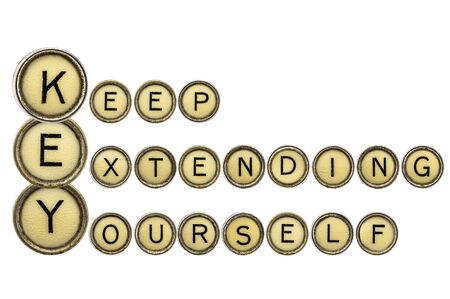 extending: KEY - keep extending yourself - motivation acronym explained in isolated vintage typewrtier keys Stock Photo