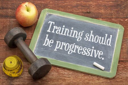 progressive: training should be progressive -  slate blackboard sign against weathered red painted barn wood with a dumbbell, apple and tape measure Stock Photo
