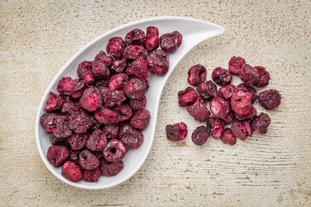 freeze dried: Freeze dried cherries in a teardrop bowl against rustic barn wood.