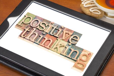 positive thinking typography - isolated text in letterpress wood type blocks on a digital tablet with a cup of tea
