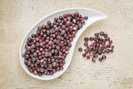 battling: Freeze dried elderberries in a teardrop bowl against rustic barn wood. Elderberries are rich in antioxidants and minerals which make them perfect in battling the common cold.