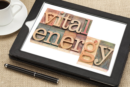 vital: vital energy typography - text in letterpress wood type blocks on a digital tablet with cup of coffee