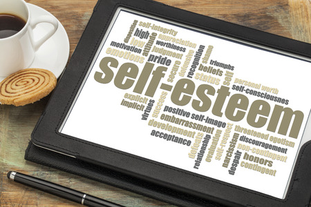 low self esteem: self-esteem word cloud on a digital tablet with cup of coffee