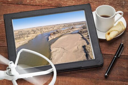 aerial landscape photography concept - reviewing aerial pictures of  the South Platte RIver in Colorado on a digital tablet with a drone rotor and cup of coffee, screen picture copyright by the photographer