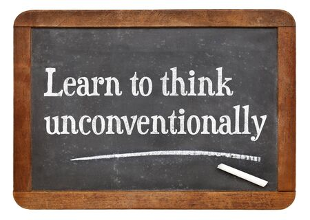 unconventionally: Learn to think unconventionally - motivational words  on a vintage slate blackboard