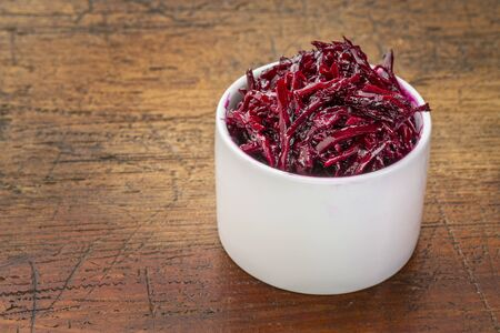 pickled: pickled beets, dulse and kale salad in a tasting bowl against rustic wood