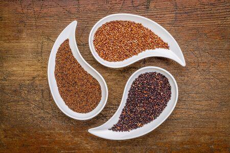 teardrop: kaniwa, red and black quinoa - three gluten free grains in teardrop shaped bowls against rustic wood