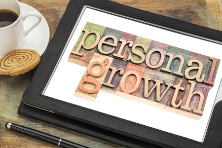 personal growth: personal growth typography - text in letterpress wood type on a digital tablet with a cup of coffee