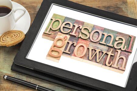 persoonlijke groei: persoonlijke groei typografie - tekst in boekdruk hout op een digitale tablet met een kopje koffie Stockfoto