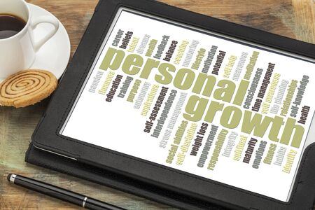 personal growth word cloud on a digital tablet with a cup of coffee photo