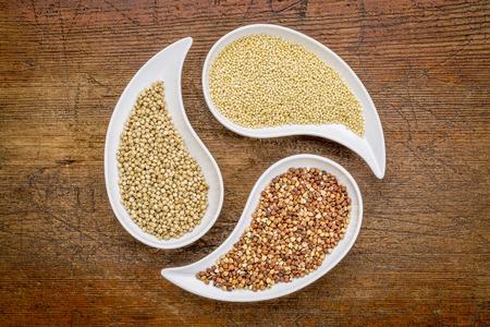 teardrop: sorghum, millet and buckwheat - three gluten free grains in teardrop shaped bowls against rustic wood Stock Photo