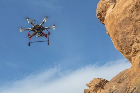 airborne vehicle: FORT COLLINS, CO, USA, February 12,  2015:  F550 Flame Wheel  hexacopter drone is  flying with a camera along sandstone cliff. Editorial
