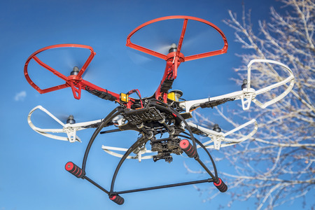 airborne vehicle: FORT COLLINS, CO, USA, December 20,  2014:  DJI  F550 Flame Wheel  hexacopter drone, assembled from a kit, flying in a backyard among trees.