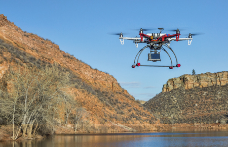 fort collins: FORT COLLINS, CO, USA, February 18,  2015:  F550 Flame Wheel  hexacopter drone is  flying with a camera over mountain lake