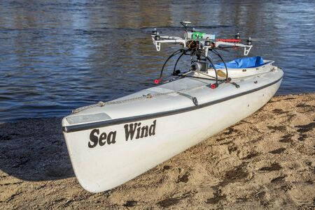 taking off: WILDCAT, CO, USA, March 9,  2015:  DJI F550 Flame Wheel  hexacopter drone with camera is taking off from a canoe deck on a river shore.