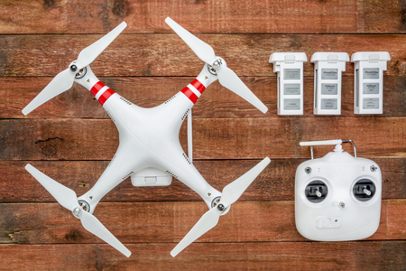 phantom: Fort Collins, CO, USA - March 17, 2015:  DJI Phantom 2 with a radio controller and spare LiPo batteries, top view against rustic wooden wood table Editorial