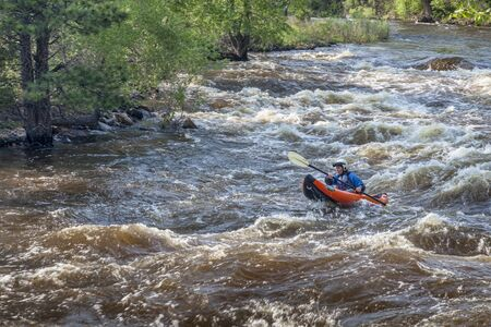FORT COLLINS, COLORADO, USA - JUNE 4, 2011: Female kayaker paddling inflatable boat over Maddog Rapid on Cache la Poudre River west of Fort Collins, Colorado as the snow pack in the high country begins to melt.