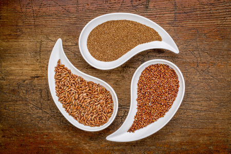 red quinoa: teff, red quinoa and brown rice - three gluten free grains in teardrop shaped bowls against rustic wood Stock Photo