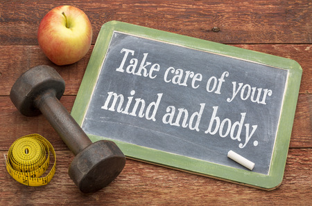 Take care of your mind and body -  slate blackboard sign against weathered red painted barn wood with a dumbbell, apple and tape measure