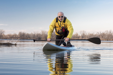 paddling: Senior male on stand up paddling (SUP) board. Early spring on calm lake in Colorado. Editorial