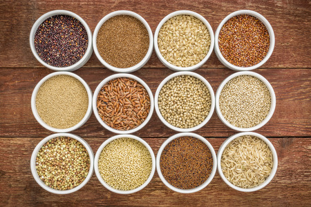 rice grain: healthy, gluten free grains collection (quinoa, brown rice, millet, amaranth, teff, buckwheat, sorghum) , top view of small round bowls against rustic wood Stock Photo