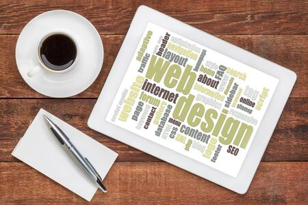 web design word cloud on a digital  tablet with a cup of coffee on a rustic wooden table