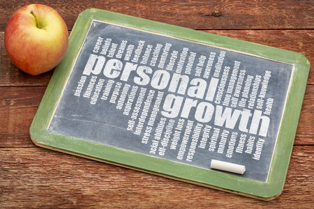personal growth word cloud on a slate blackboard with apple photo