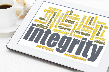 trust: integrity word cloud on digital tablet with a cup of coffee