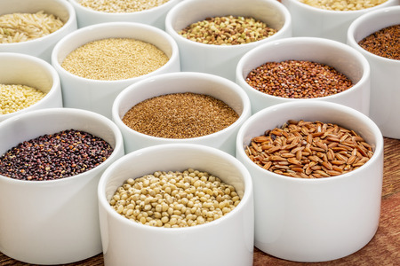 healthy, gluten free grains collection (quinoa, brown rice, millet, amaranth, teff, buckwheat, sorghum), small round bowls against rustic wood Stockfoto