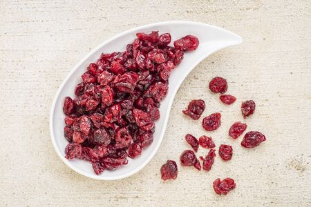 dried cranberry on a teardrop shaped bowl against a rustic barn wood