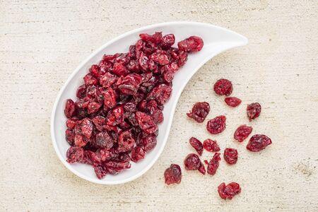 teardrop: dried cranberry on a teardrop shaped bowl against a rustic barn wood