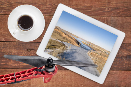 horsetooth reservoir: aerial landscape photography concept - reviewing aerial pictures of  the Horsetooth Reservoir in Colorado on a digital tablet with a drone rotor in foreground, screen picture copyright by the photographer