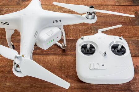 Fort Collins, CO, USA - March 17, 2015:  DJI Phantom 2 quadcopter drone with a radio controller against rustic wooden wood table Publikacyjne