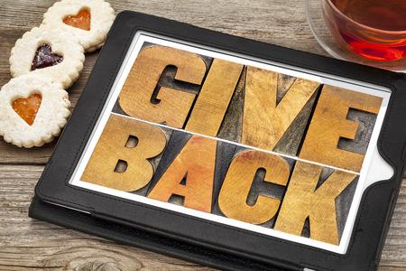 espalda: devolver palabras de texto en el tipo de madera de tipografía en una tableta digital con té y galletas del corazón