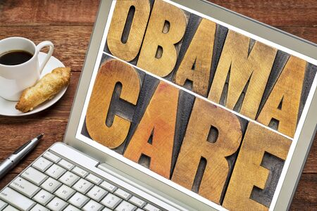 obamacare typography - word abstract in letterpress woodtype on a laptop screen photo