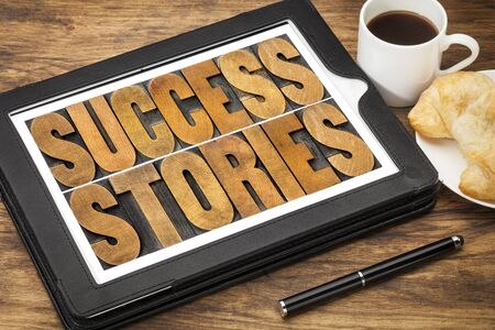 testimony: success stories typography - word abstract in vintage letterpress wood type on a digital tablet with a cup of coffee