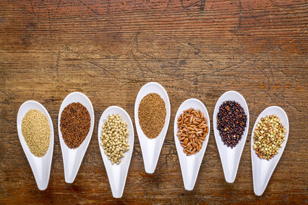 seven healthy, gluten free grains (quinoa, brown rice, amaranth, teff, buckwheat, sorghum. kaniwa), top view of small spoons against rustic wood with a copy space Stock Photo