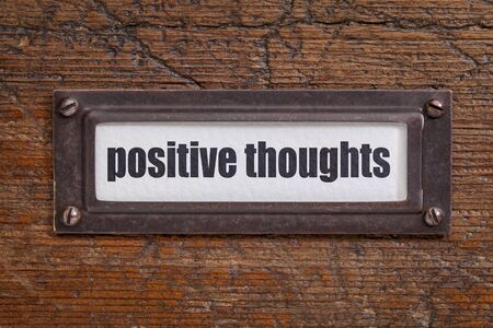 positive thoughts  - file cabinet label, bronze holder against grunge and scratched wood Stock fotó