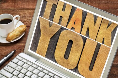 wood type: thank you - word abstract in letterpress wood type on a laptop screen Stock Photo