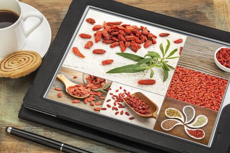 superfruit: reviewing and editing pictures of goji berries on a digital tablet Stock Photo
