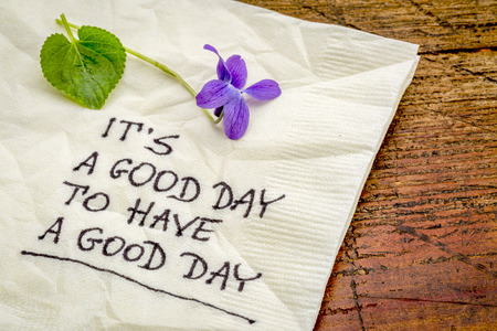 good: it is a good day  to have a good day - handweiting on a cocktail napkin with a viola flower
