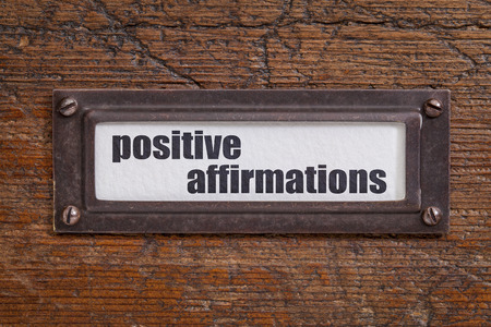 affirmations: positive affirmations - file cabinet label, bronze holder against grunge and scratched wood Stock Photo