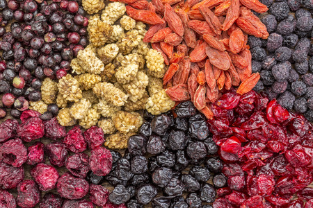 superfruit: background of healthy dried superfruit berries - blueberry, mulberry, cherry, goji, elderberry, chokeberry, and cranberry