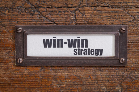 win-win strategy  - file cabinet label, bronze holder against grunge and scratched wood Banque d'images
