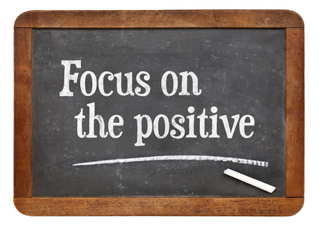Focus on the positive - inspirational advice n on a vintage slate blackboard Banco de Imagens