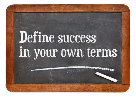define: Define success in your own terms - inspirational words on a vintage slate blackboard