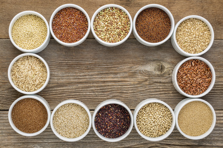 healthy, gluten free grains collection (quinoa, brown rice, millet, amaranth, teff, buckwheat, sorghum) , top view of small round bowls against rustic wood with a copy space Stock Photo