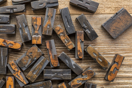 wood type: vintage letterpress wood type printing blocks stained by inks placed randomly on a wooden table