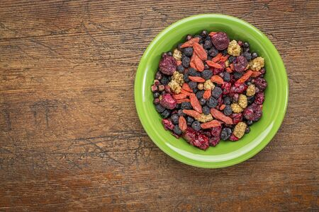 superfruit: superfruit berry mix (blueberry, mulberry, cherry, goji, elderberry, chokeberry, and cranberry) - green ceramic bowl against grunge wood Stock Photo